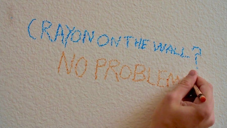 Someone writing on the wall 'Crayon on the wall? No problem.""