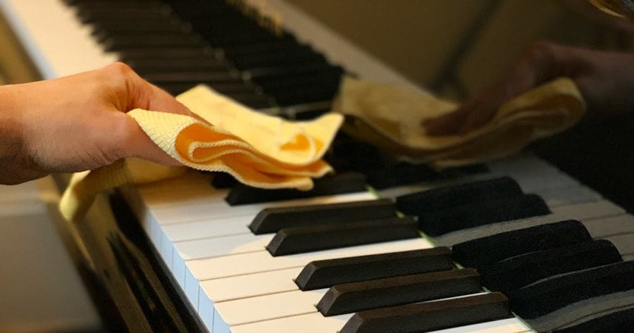 Wiping the vinegar off of piano keys using a microfiber cloth.