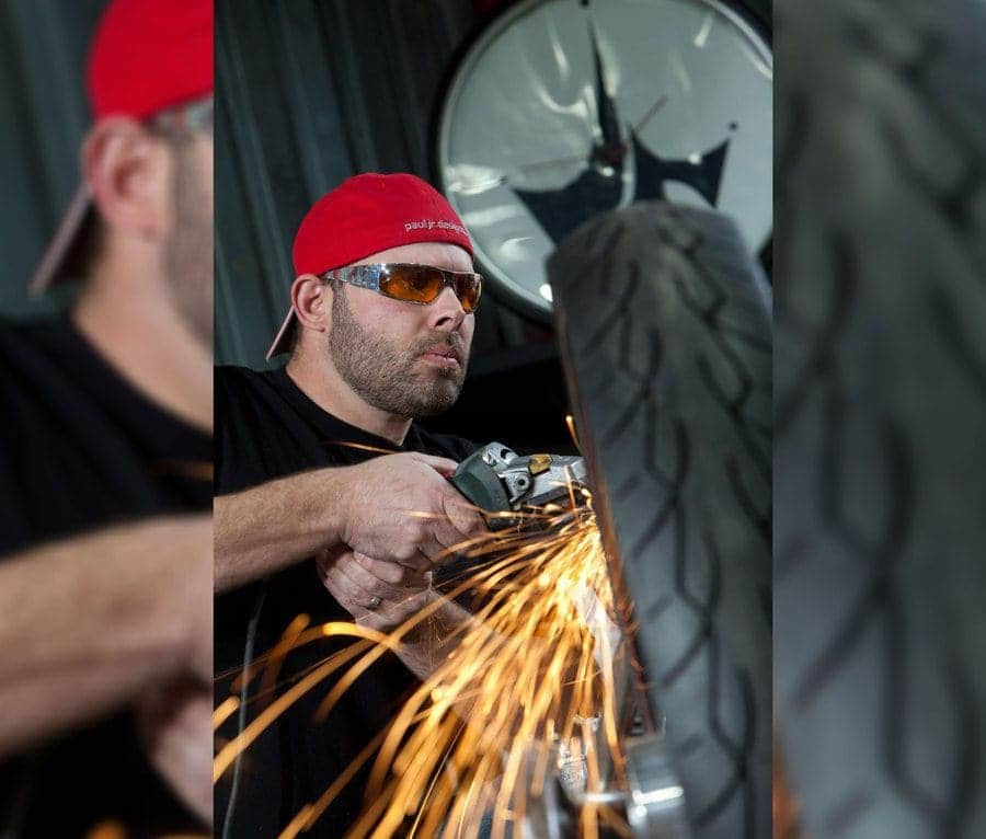 Paul Jr. is welding metal near a bike tire