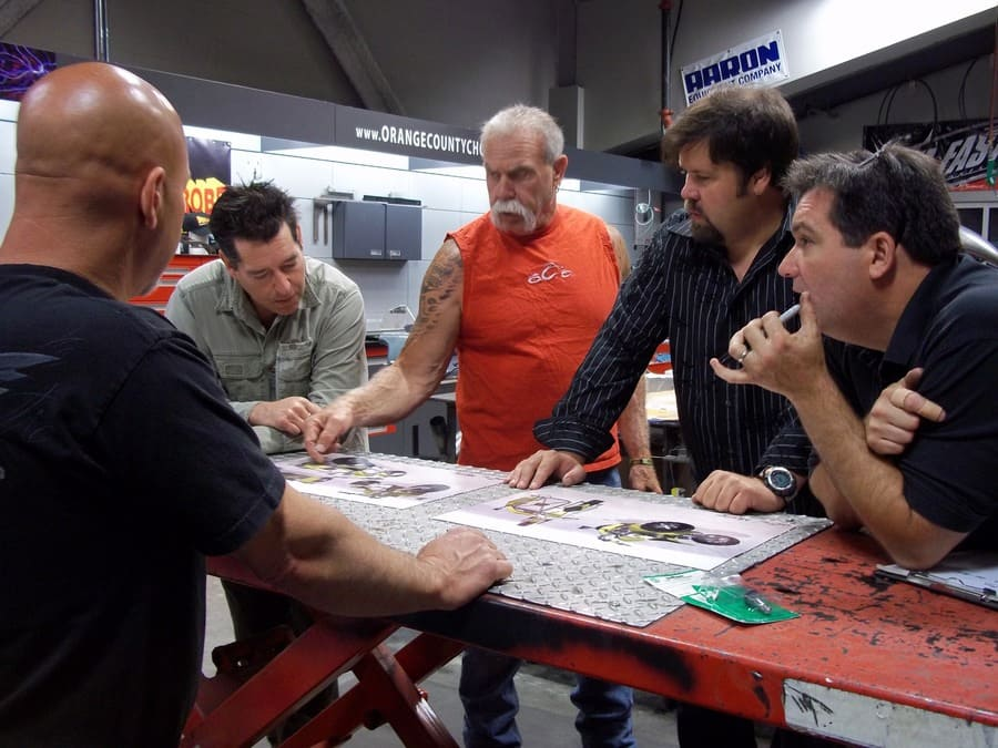 Paul Sr. is standing around a table looking at a design at the shop with other workers