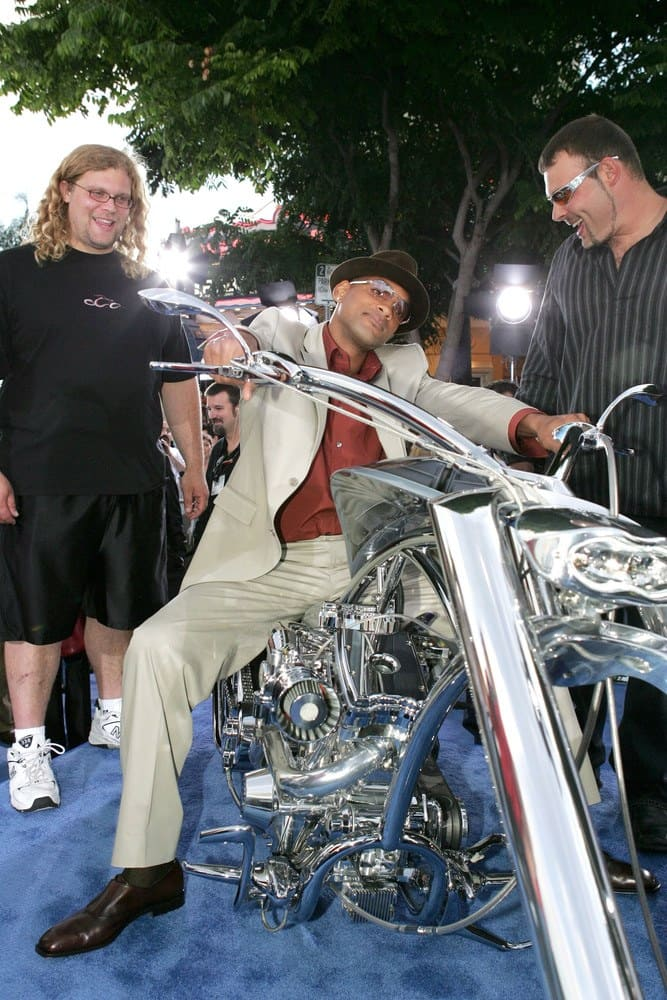 Mikey and Paul Jr. are with Will Smith, who is sitting and posing on a bike