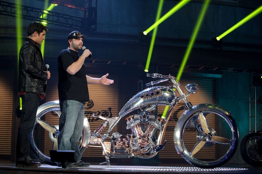 Paul Jr on stage with a bike and a show host