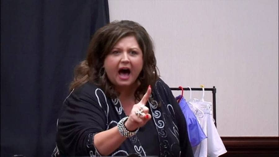 Abby Lee Miller is screaming angrily with her finger pointed forward.