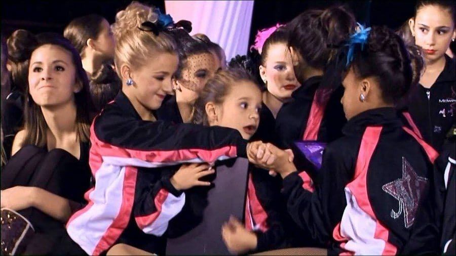 The Dance Moms girls are on stage waiting to hear the judge's final scores.