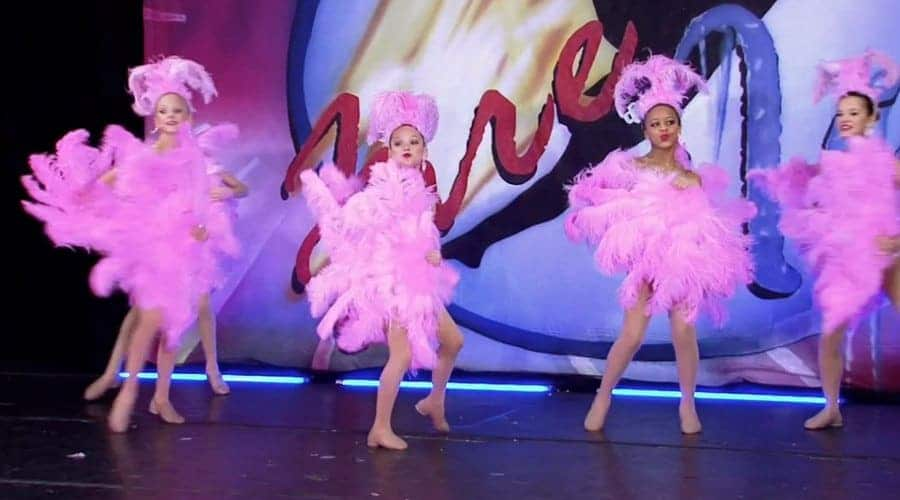 The girls are on stage performing the showgirls dance.