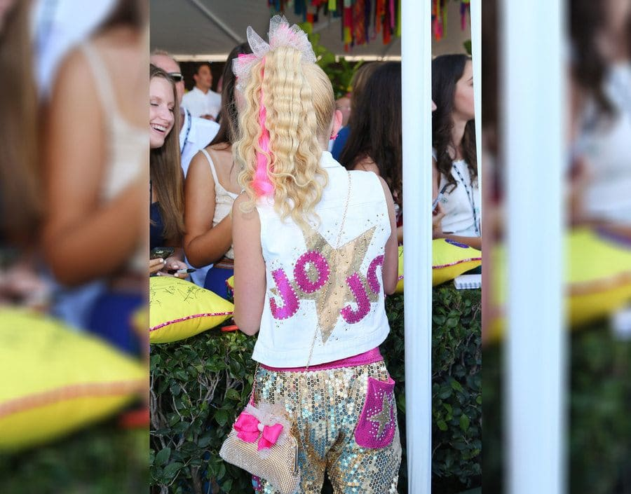 A photograph of JoJo Siwa from behind with her hair in a high ponytail with a pink streak, crimped, and with a large white bow. Her vest has a gold star, and her name bedazzled in hot pink across it.