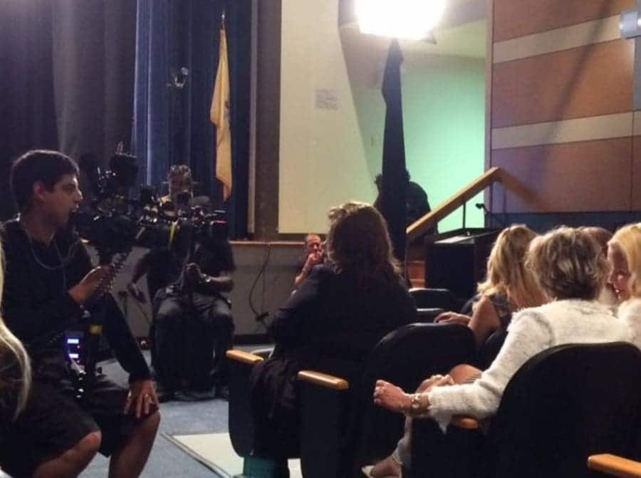 Abby Lee Miller is sitting in the front row at a competition with the cameras aimed toward her.