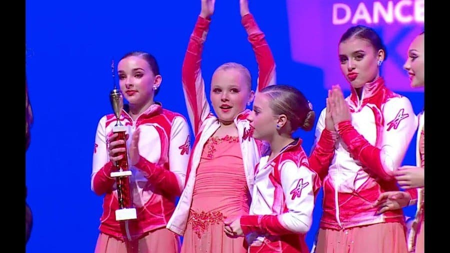 The girls are on stage at a competition holding an award.