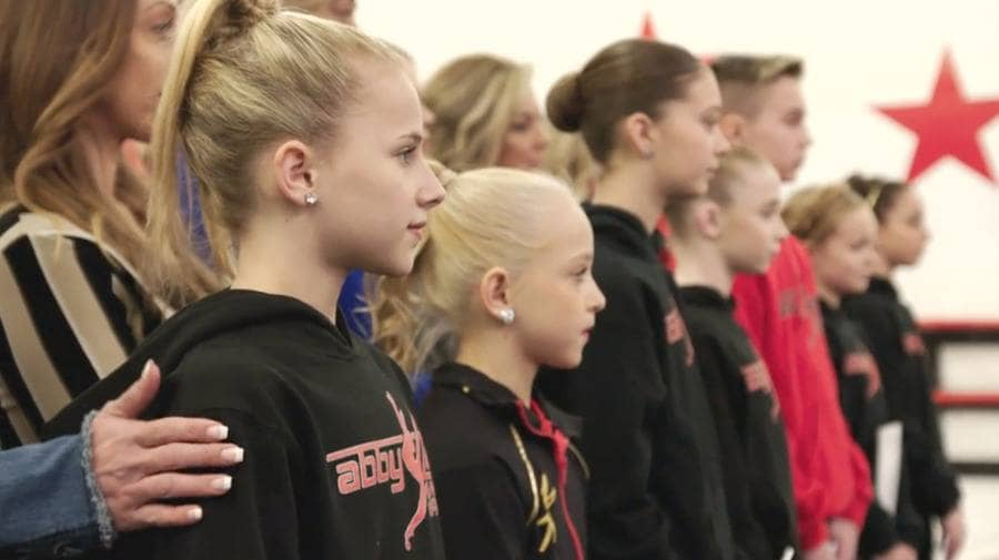 The dancers are lined up with their moms standing behind them from an episode of Dance Moms.