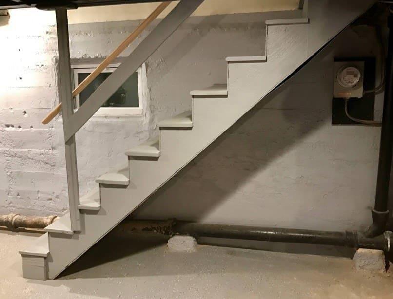 El sótano vacío antes de empezar a trabajar en él, con los escalones que bajan por el lado de la pared.