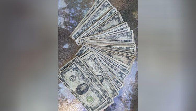Un fajo de billetes de 20 abanicados sobre la mesa