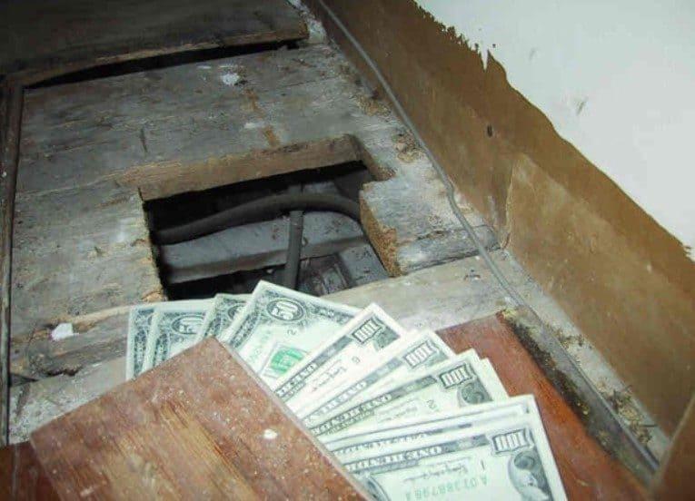 Billetes de $50 y $100 abanicados en el piso viejo.