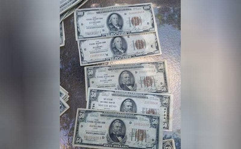 Viejos billetes de 50 dólares alineados en una mesa de vidrio.