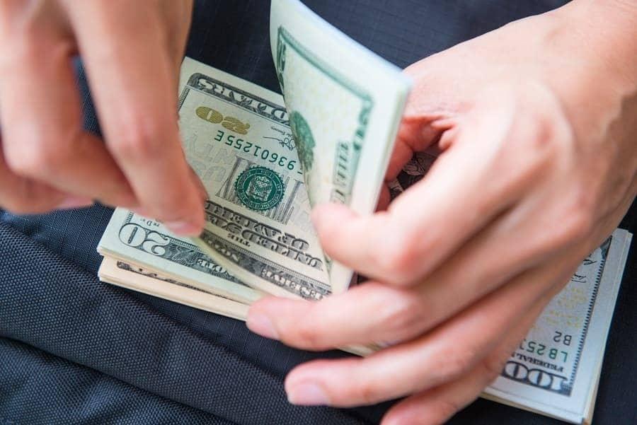 Una mujer sujeta mientras cuenta, un puñado de billetes de 100 y 20 dólares.