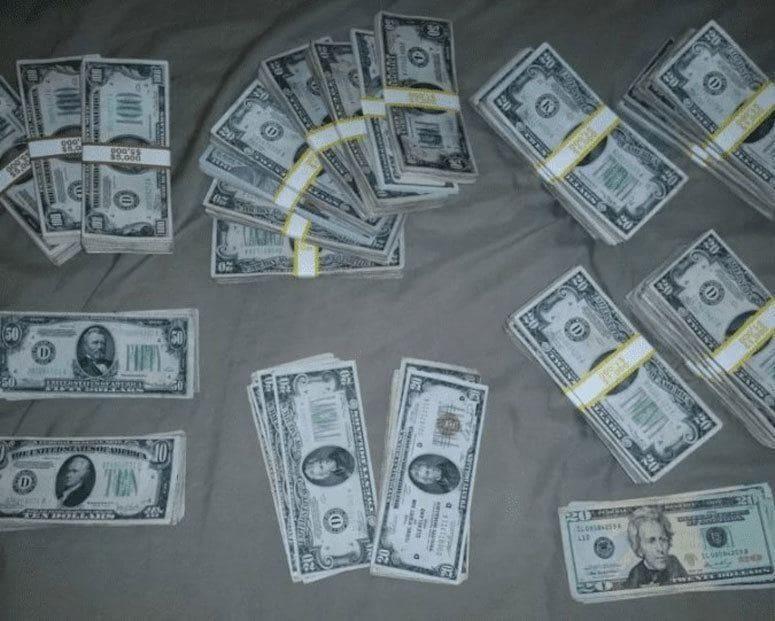 Montones de billetes de 100, 50, 20 y 10 dólares tirados en una cama.