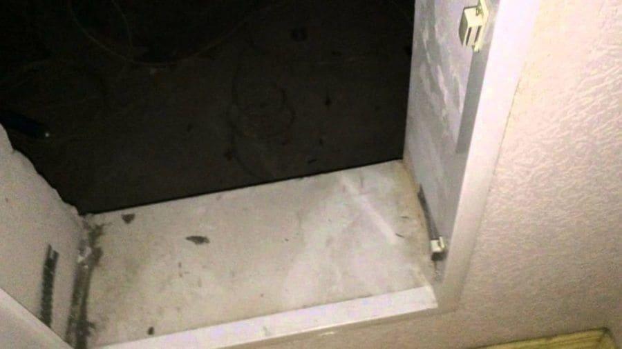 La misteriosa puerta abierta con una vista oscura directo al suelo del interior.