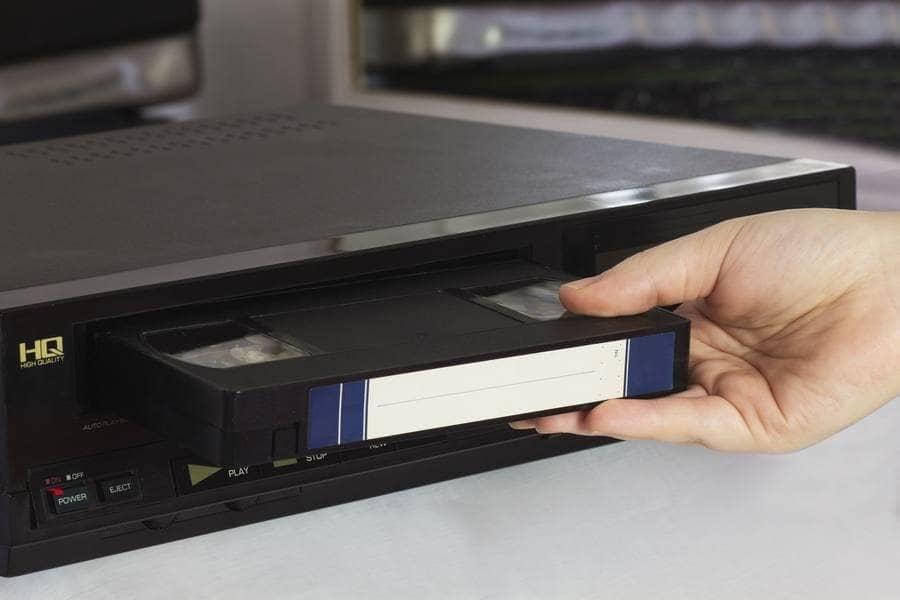 Alguien coloca una cinta VHS en un reproductor.