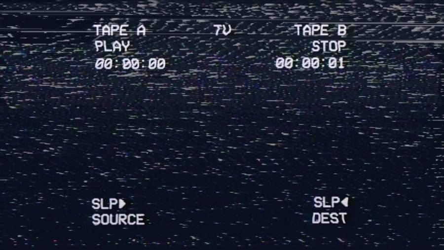 Una vieja cinta VHS siendo reproducida con la fecha en la esquina inferior y la distorsión en blanco y negro a través de la pantalla.