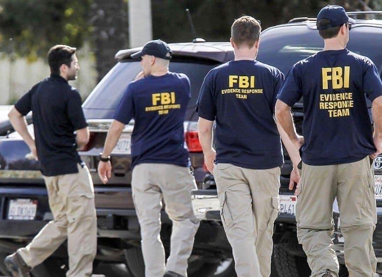 Unos cuantos miembros del equipo de evaluación de pruebas del FBI caminando alrededor