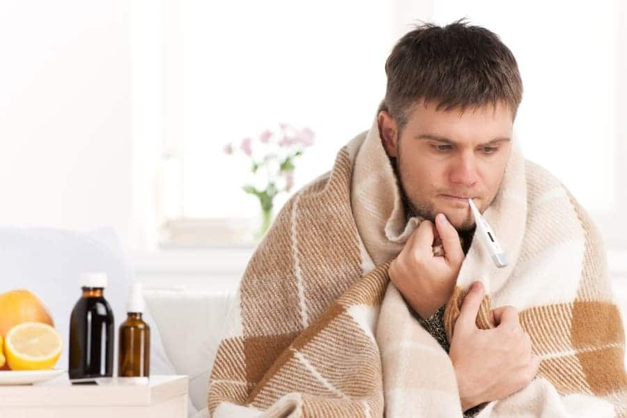 Man with cold sitting on a sofa with a thermometer in mouth