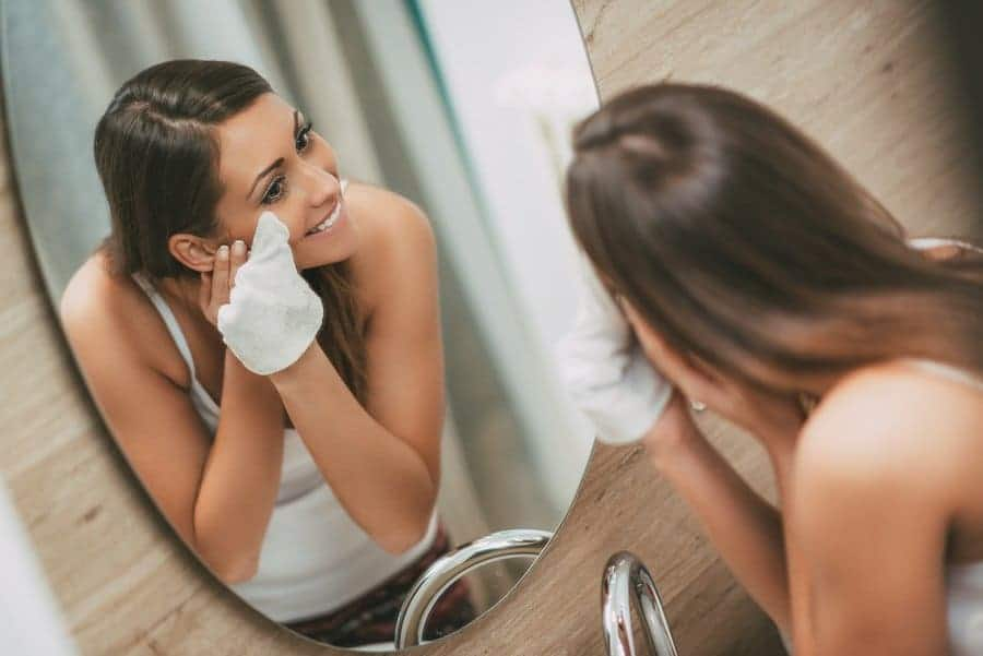 woman removing makeup in front of a mirror