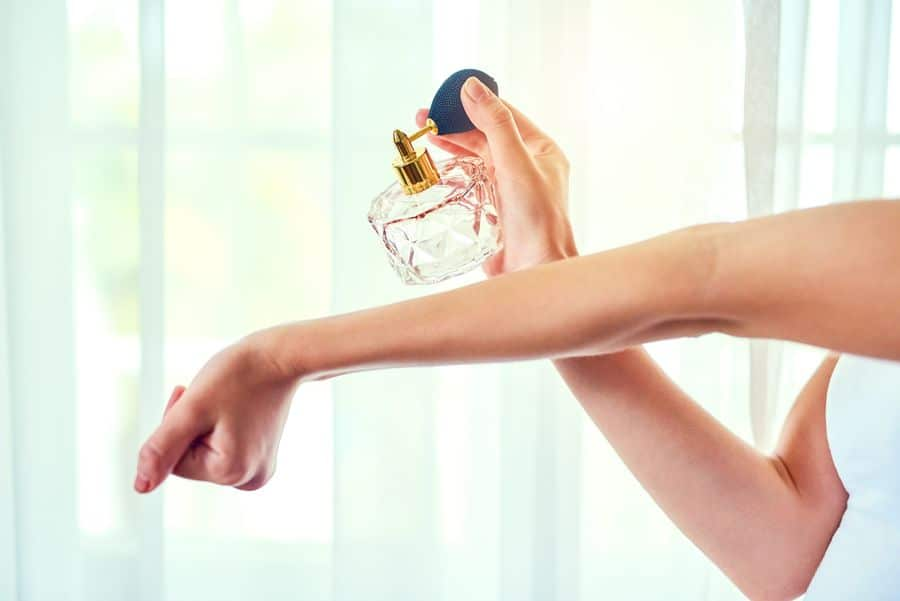 Women putting perfume on the arm