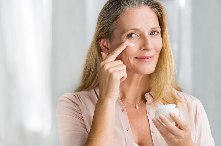 Smiling senior woman applying anti-aging lotion to remove dark circles under eyes
