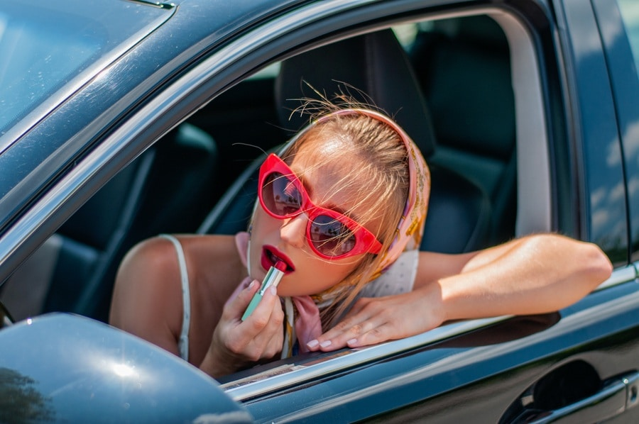 Beautiful fashion woman putting on lipstick while driving in the car.