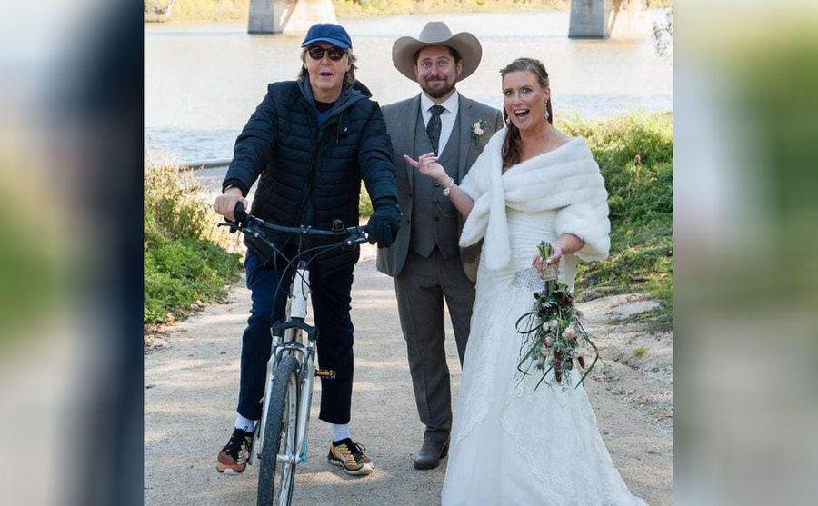 Paul McCartney on his bike posing with newlyweds
