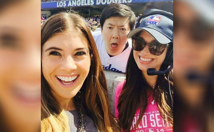 Ken Jeong posing behind two girls at an LA Dodgers game