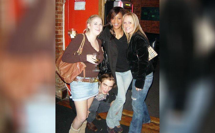 Robert Pattinson peeking out from behind the legs of three girls posing