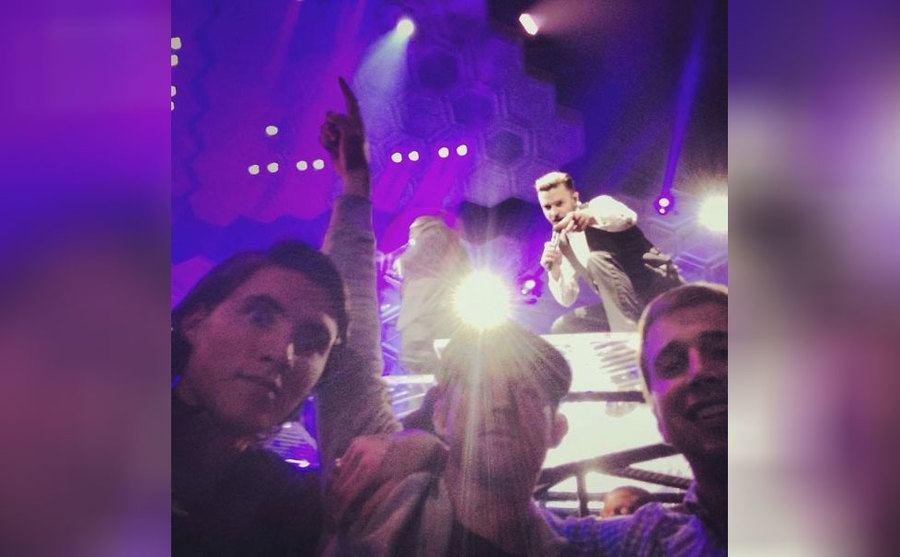 Justin Timberlake on stage performing behind three people taking a selfie