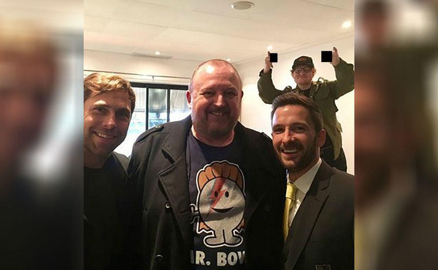 Ed Sheeran behind a group of guys taking a photograph