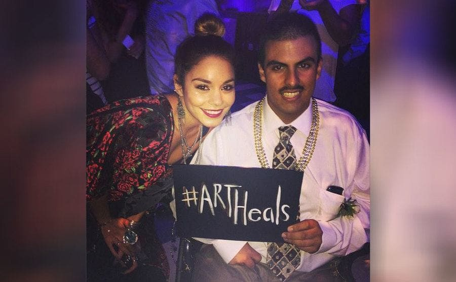 Vanessa Hudgens and Cesar Guerro with a sign that says 'hashtag art heals'