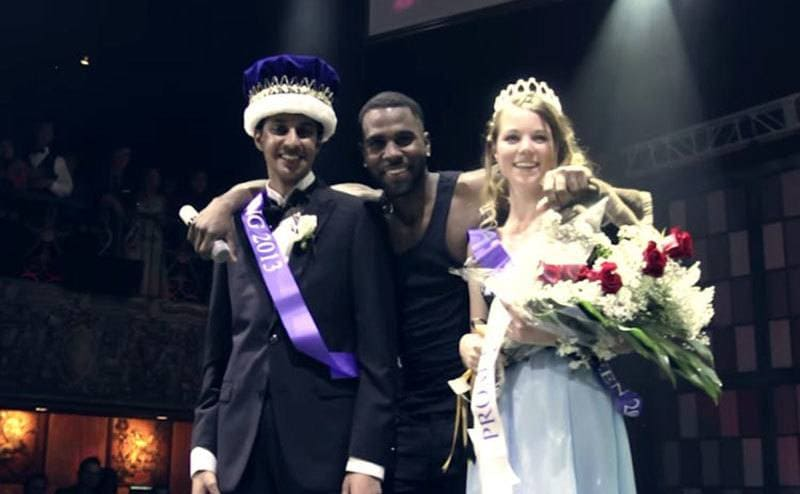 Jason Derulo with the prom king and queen with crowns and the prom queen holding flowers on stage