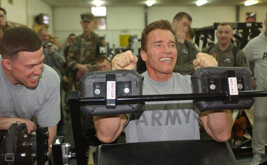 Arnold Schwarzenegger working out in a shirt that says 'ARMY.'