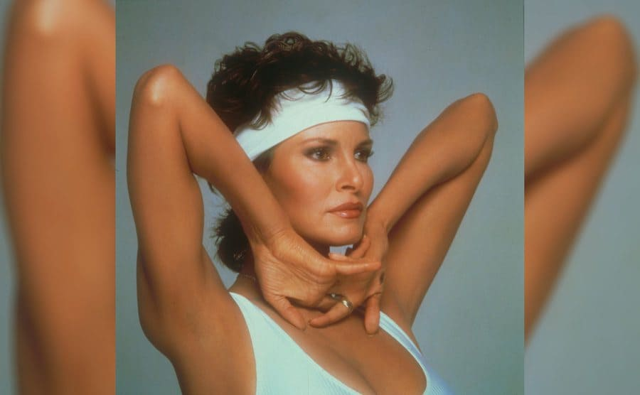 Raquel Welch in a white bodysuit with a matching headband holding her elbows upward, but her hands clasped underneath her chin