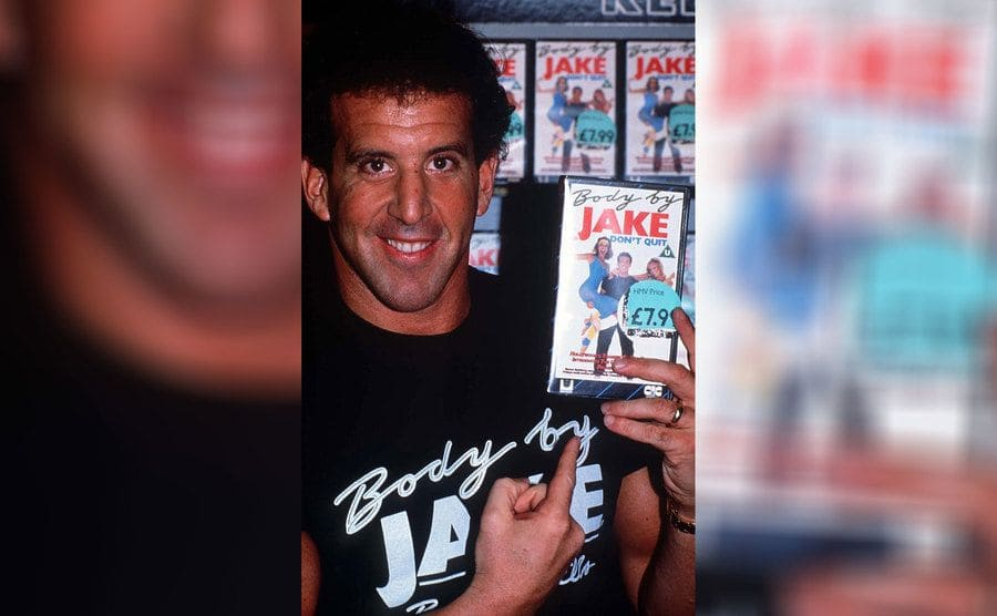 Jake Steinfeld in a black 'Body by Jake' t-shirt holding up a 'Body by Jake' VHS tape