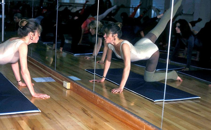 Jane Fonda in a white leotard directing a fitness class for the stars in 1980