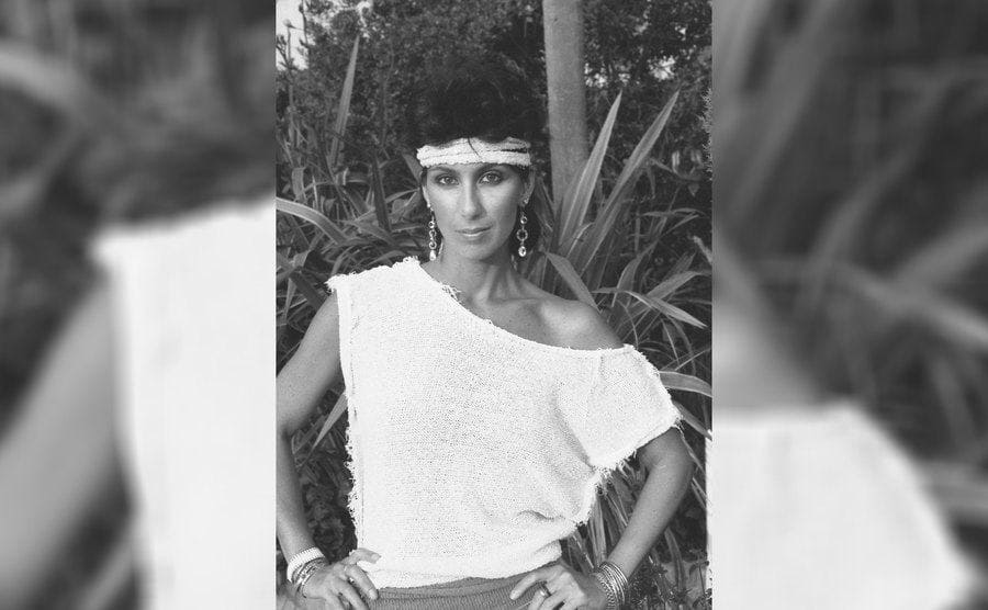 Cher in St Tropez, France, wearing an off the shoulder shirt and headband in the '80s