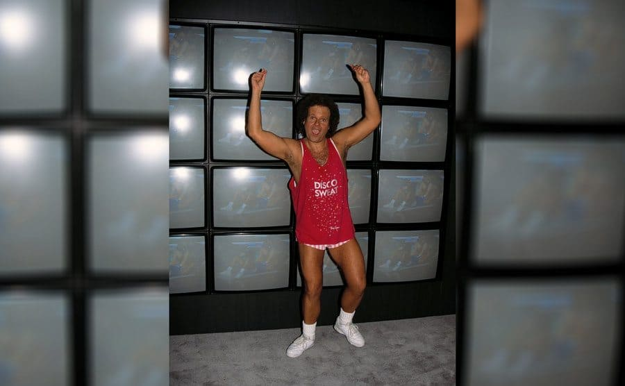 Richard Simmons in his '80s workout gear that says 'Disco Sweat' on it, waving his hands in the air