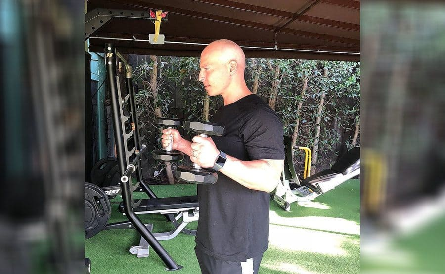 Harley Pasternak holding a weight in an outdoor home gym