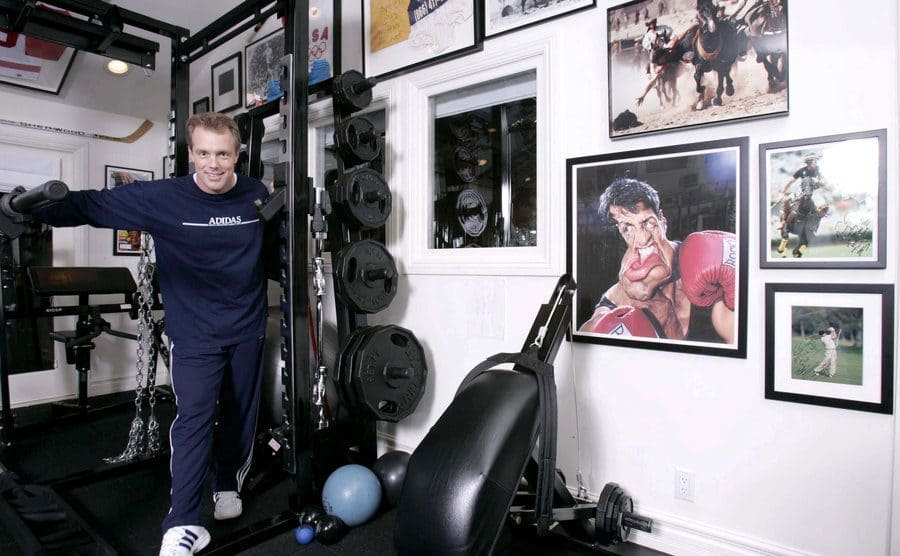 Gunner Peterson is standing by his weights in a home gym with athlete's photographs all over the wall
