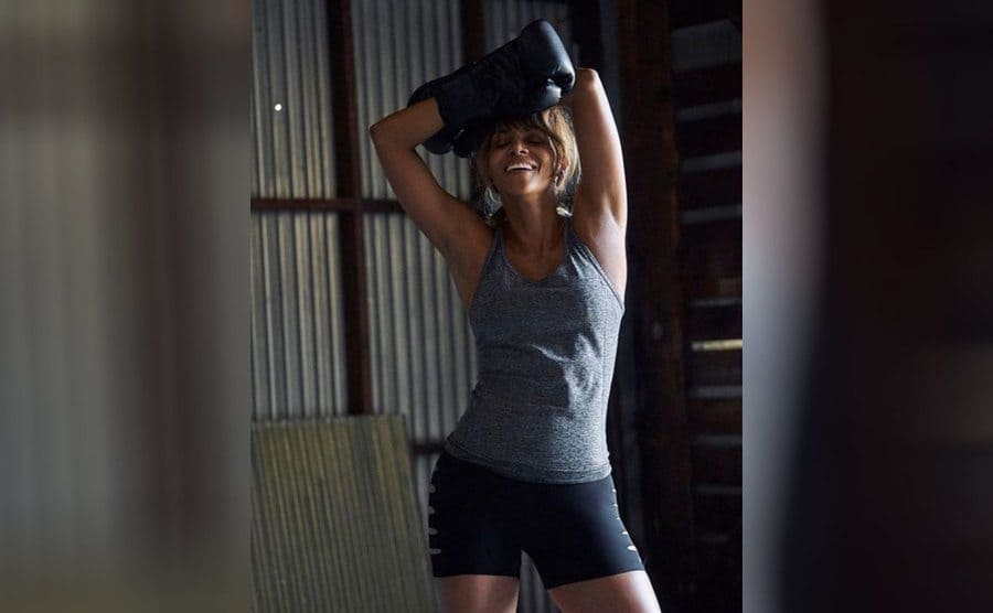 Halle Berry in workout shorts and a tank top with boxing gloves on