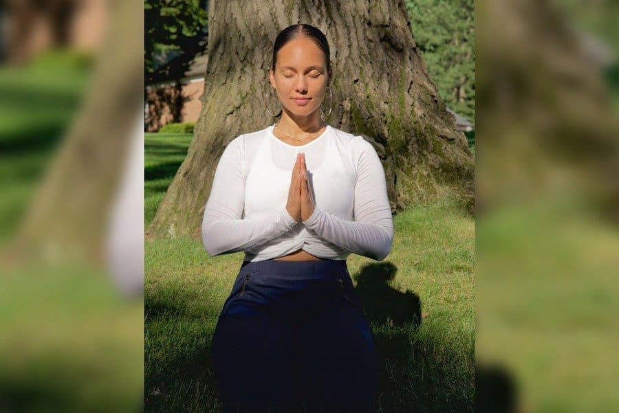 Alicia Keys in a yoga pose in the middle of the grass with the sun shining through the trees behind her