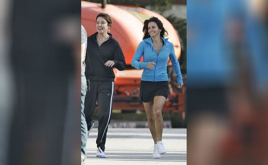 Courtney Cox and Christa Miller are wearing workout gear and jogging while filming Cougartown
