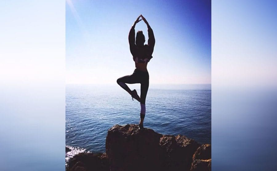 Kendall Jenner doing yoga on a rock in front of the ocean