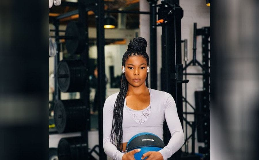 Gabrielle Union posing at the gym in front of the weights