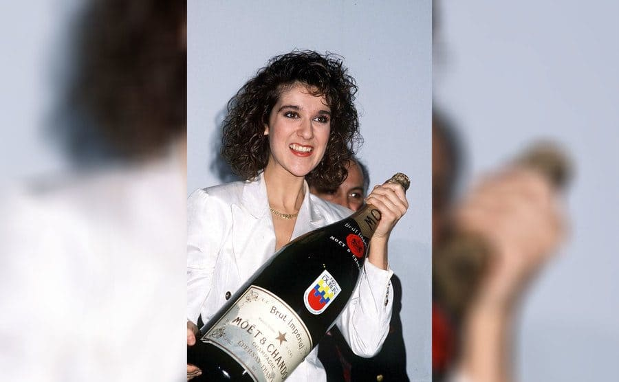 Celine Dion is holding an extra-large bottle of champagne after winning Eurovision for Switzerland, 1988.