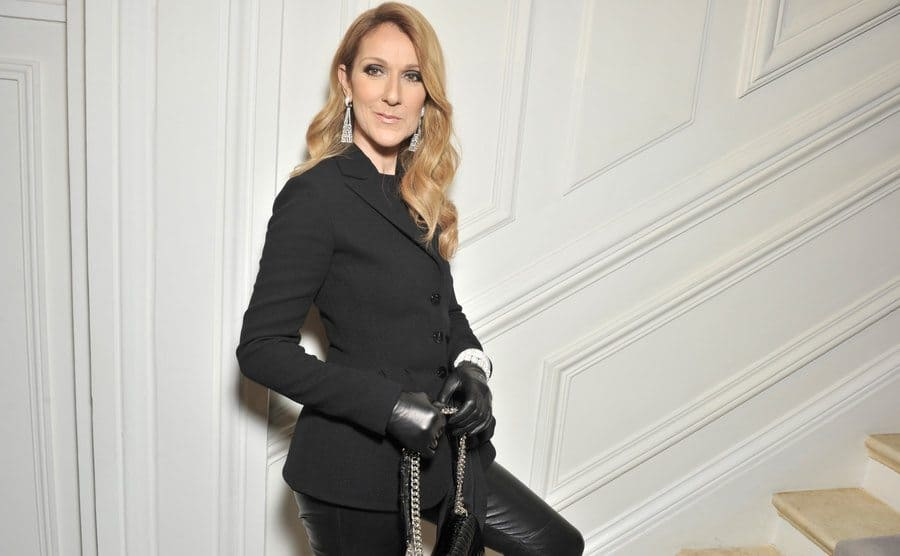 Celine Dion was standing at the bottom of a staircase dressed in all black, including black gloves and a purse, with one foot on the first step.